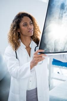 Raggi x della colonna vertebrale della tenuta del fisioterapista del paziente
