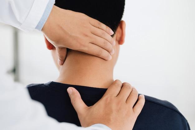 Fisioterapista massaggiatore che tiene la testa dei clienti di sesso maschile e massaggia i muscoli del collo stretti