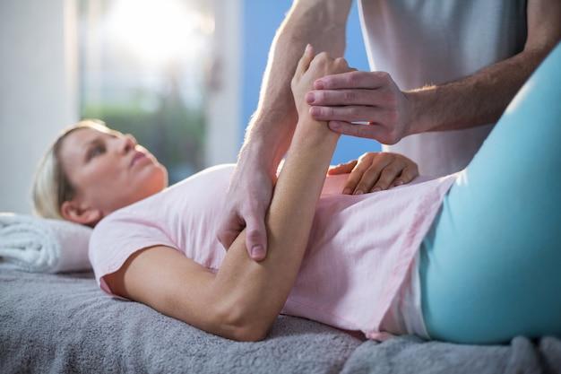Fisioterapista che massaggia la mano di una paziente