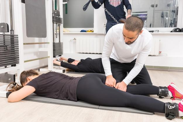 Fisioterapista che massaggia donna sdraiata sulla stuoia durante l'allenamento in palestra