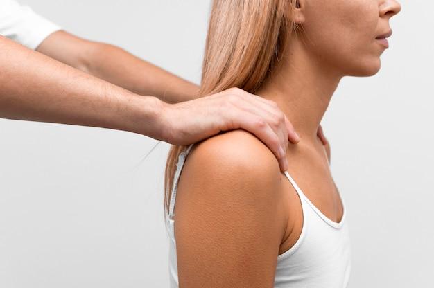 Fisioterapista che massaggia la spalla della donna