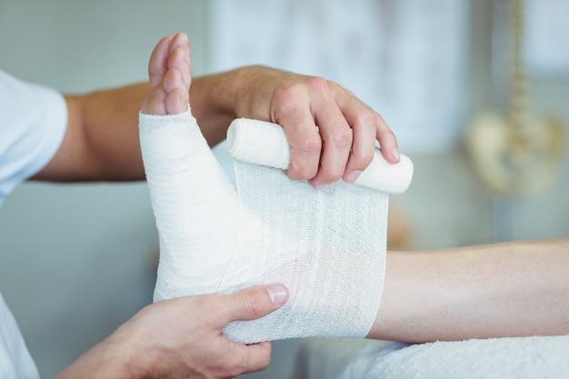 Fisioterapista che mette fasciatura sui piedi feriti del paziente