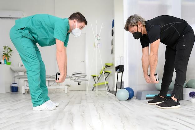 Fisioterapista che mostra i movimenti della terapia riabilitativa per paziente maschio.