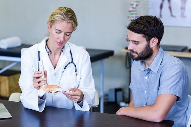 Fisioterapista che mostra un modello di piedi scheletro al paziente