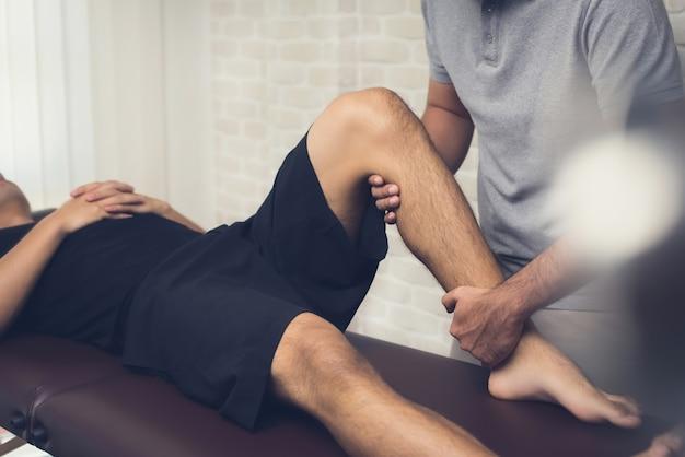 Fisioterapista che tratta il paziente maschio dell'atleta