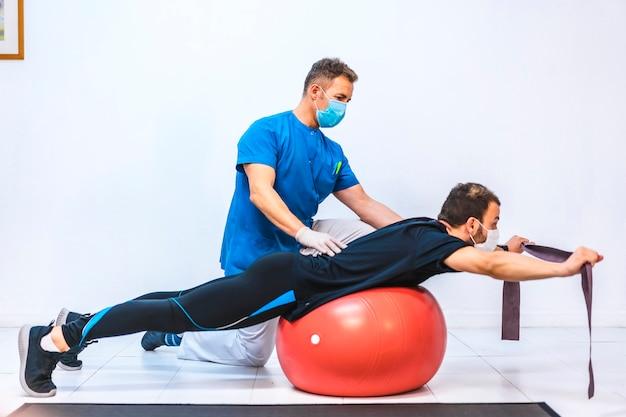 Fisioterapista con maschera e un paziente facendo esercizi con una gomma su una palla gigante. fisioterapia con misure protettive per la pandemia di coronavirus, covid-19. osteopatia, chiromassaggio sportivo
