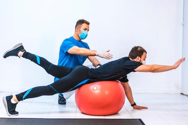 Fisioterapista con maschera e un paziente che si estende su una palla. fisioterapia con misure protettive per la pandemia di coronavirus, covid-19. osteopatia, chiromassaggio sportivo
