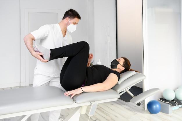 Fisioterapista con maschera protettiva che dà un massaggio a un paziente. riapertura con misure di sicurezza fisioterapica nella pandemia covid-19. osteopatia, chiromassaggio terapeutico.