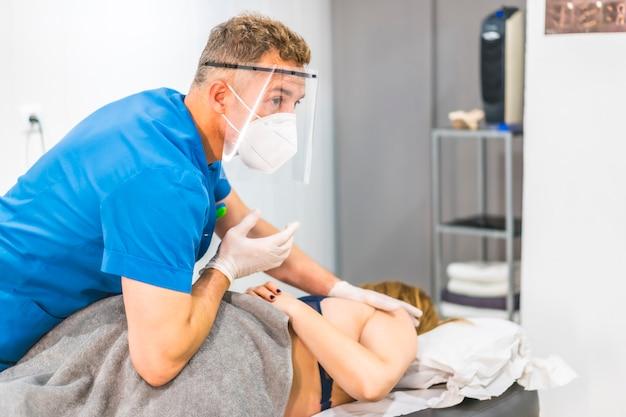 Fisioterapista con schermo e maschera per un massaggio dell'anca. riapertura con misure di sicurezza per fisioterapia nella pandemia di covid-19. osteopatia, chiromassaggio terapeutico