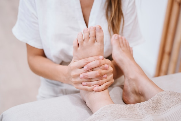 Fisioterapista donna che dà un massaggio ai piedi al paziente in clinica