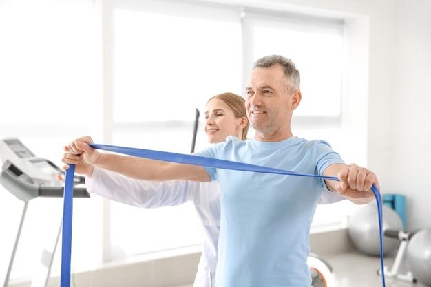 Fisioterapista che lavora con paziente maturo nel centro di riabilitazione