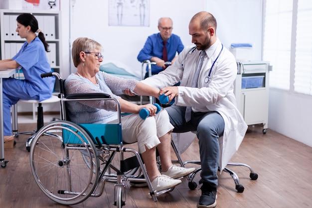 Fisioterapia per donna anziana in sedia a rotelle per recuperare la forza muscolare nella clinica di recupero