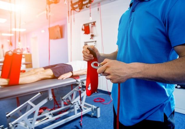 Fisioterapia. terapia di allenamento in sospensione. giovane che fa trazione fitness