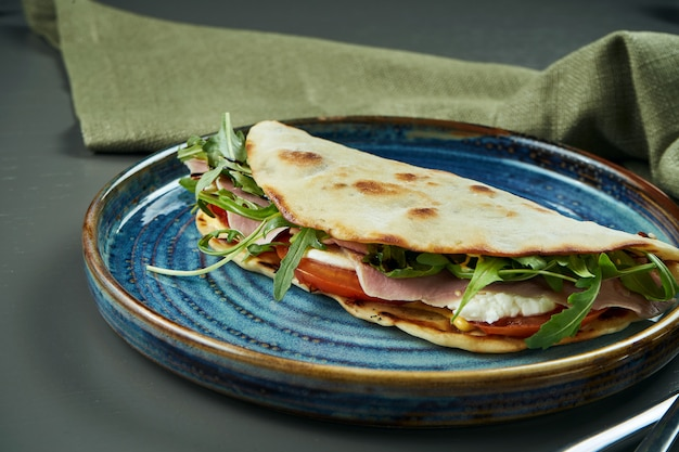 Piadina - classico tortilla-pane italiano con vitello tonato vitello, rucola, mozzarella e pomodori su un piatto blu sul tavolo di legno. sandwich veloce. primo piano, messa a fuoco selettiva