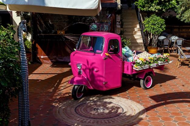 Piaggio ape di colore rosa con fiori e cose in vendita nel baule