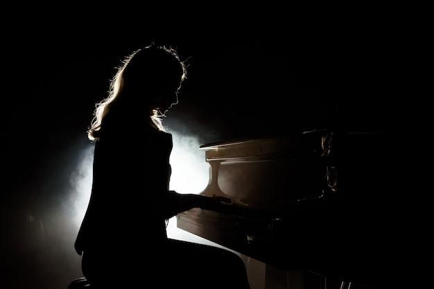 Riproduzione di musica per pianoforte musicista pianista. pianoforte a coda dello strumento musicale con l'esecutore della donna