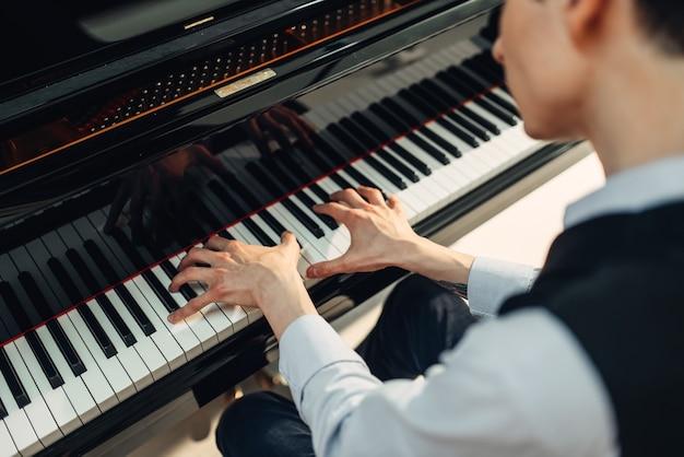 Pianista che suona musica al pianoforte a coda