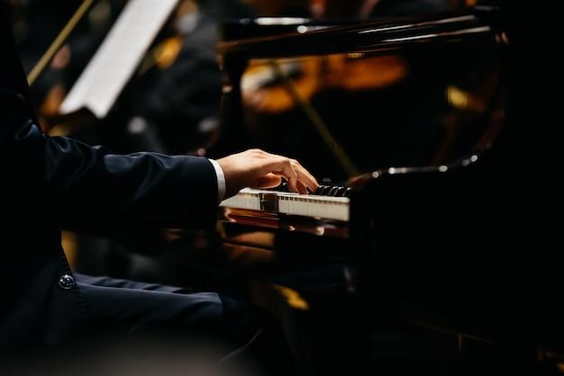 Pianista che suona un pezzo su un pianoforte a coda durante un concerto, visto di lato.