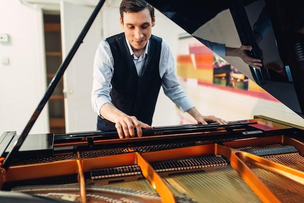 Il pianista imposta il pianoforte a coda prima della performance