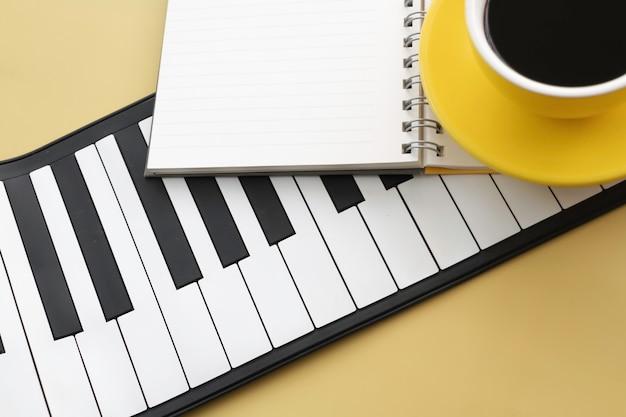 I tasti del pianoforte e il libro aperto mettono una bella tazza di ceramica gialla sfocata con caffè nero, sfondo pastello