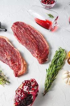 Bistecche di manzo picanha organiche con rosmarino, grani di pepe, melograno, vicino al vino rosso in bicchieri e bottiglia su sfondo bianco strutturato, vista laterale.