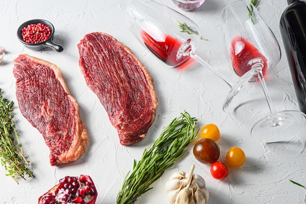 Bistecche di manzo organiche picanha con rosmarino, pepe in grani, melograno, vicino a vino rosso in bicchieri e bottiglia su sfondo bianco con texture, vista laterale.