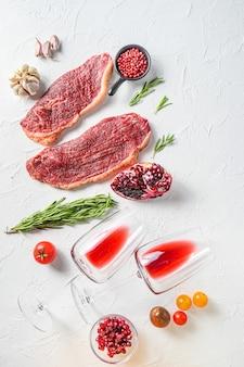 Bistecche di manzo picanha organiche con rosmarino, grani di pepe, melograno, vicino al vino rosso in bicchieri e bottiglia su sfondo bianco strutturato, vista dall'alto.
