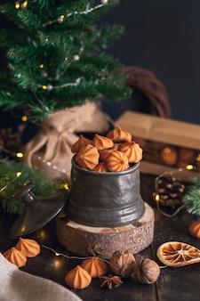 Picci - biscotti di pasta frolla di natale in vaso vintage su sfondo di rami di abete.