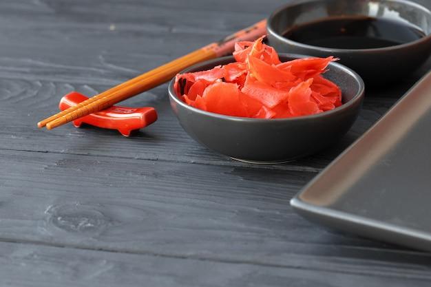 Radice di gognger marinata e salsa di soia in ciotole sulla tavola di legno