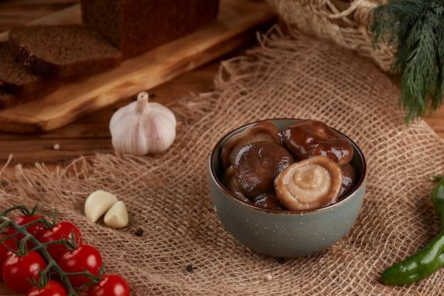 Funghi sott'aceto in una ciotola di ceramica con olio, di legno