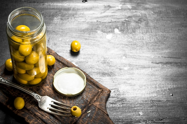 Olive in salamoia in vaso. sulla lavagna nera.