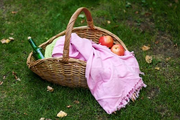 Cestino da picnic con una coperta, una bottiglia di vino e mele sull'erba autunnale