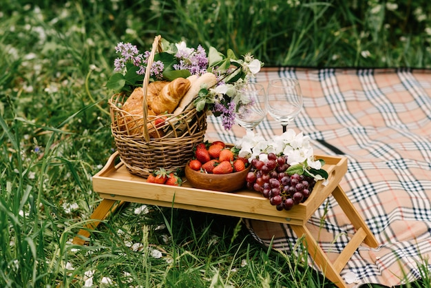 Cestino da picnic con fragole, uva e panini sull'erba verde in giardino