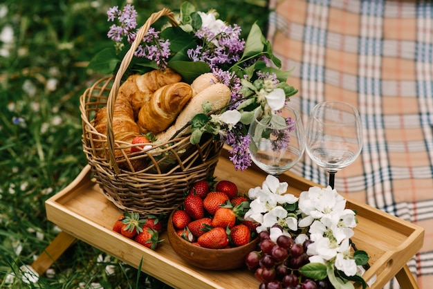 Cestino da picnic con fragole, uva e focacce sull'erba verde del giardino
