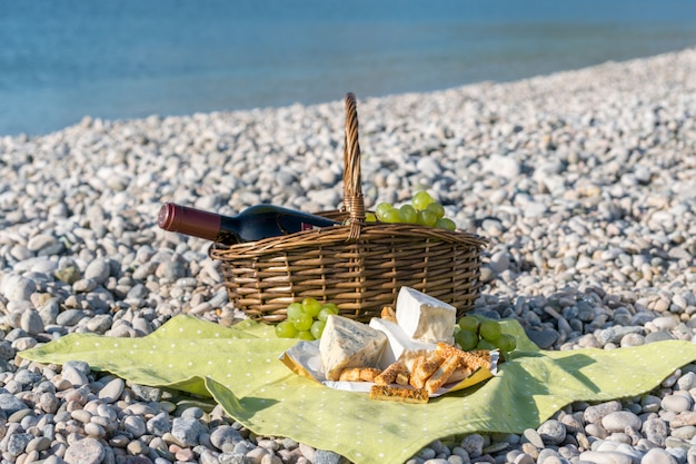 Cestino da picnic con vino, formaggio e uva