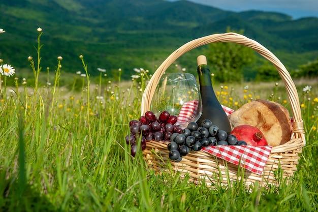 Un cestino da picnic con vino, frutta, uva e pane si trova su un prato nell'erba verde