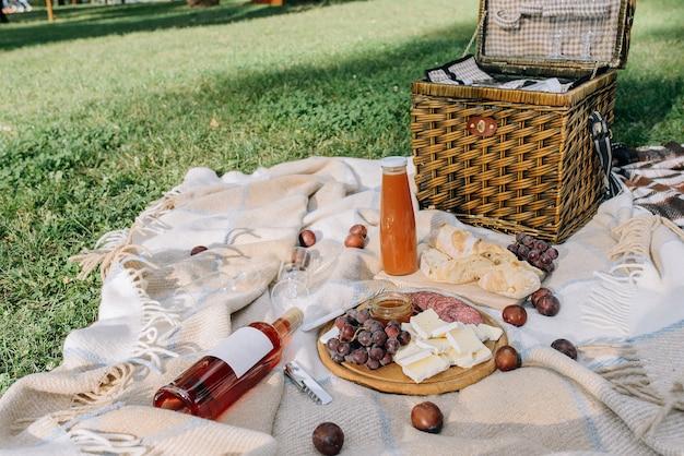 Picnic su una coperta nel parco all'aria aperta con cibo e bevande