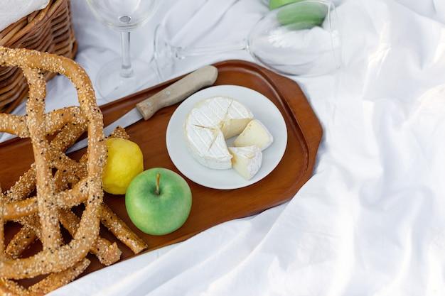 Colazione picnic all'alba, sul lenzuolo bianco d'erba con vassoio con formaggio e vite, pane secco, mela, limone. umore romantico, concetto estetico di stile di vita lento, vista dall'alto