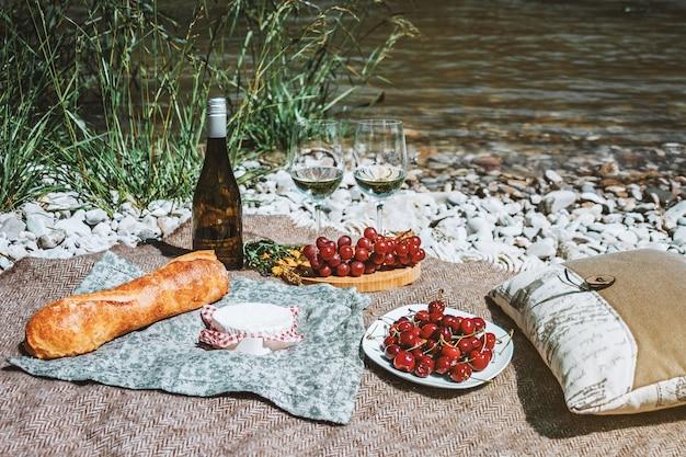 Picnic sulla costa con bicchieri di vino bianco bottiglia baguette ciliegie formaggio uva libro aperto