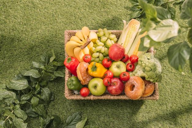 Picnic sull'erba. tovaglia a quadretti rossa, cestino, panino e frutta sani, succo d'arancia. vista dall'alto. riposo estivo. disposizione piatta.