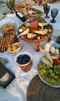 Picnic nella natura con simpatiche decorazioni da donna. frutta, vino, formaggio, dolcetti e candele