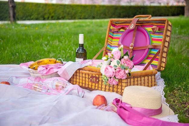 Picnic nel parco sotto i ciliegi in fiore con frutta, vino, pane e croissant