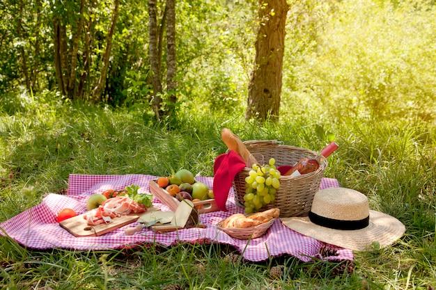 Pic-nic al parco sull'erba: tovaglia, cestino, cibo sano, vino rosato e accessori