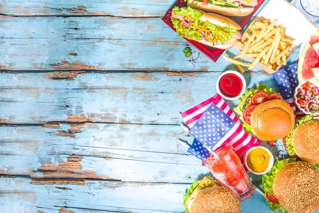Festa da picnic con anguria, hamburger, hot dog, bevande, sfondo tavolo in legno blu all'aperto