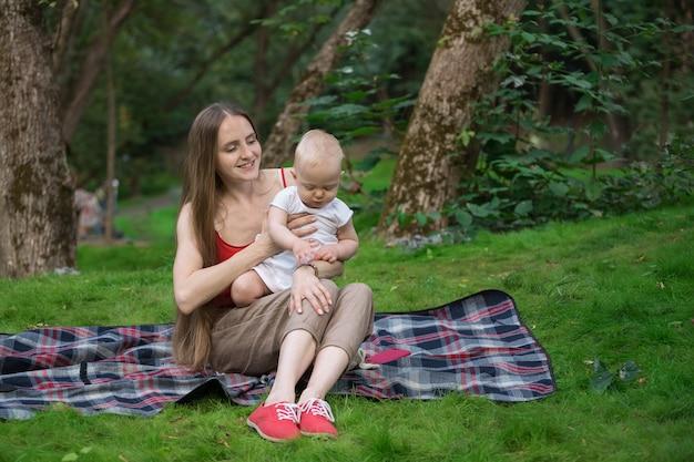 Pic-nic con bambini. concetto di rilassamento insieme con il bambino. coperta di picnic di seduta del bambino e della madre.