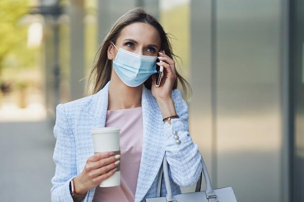 Immagine di una donna adulta attraente che indossa una maschera con uno smartphone che cammina in città
