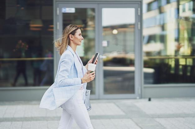 Immagine di una donna attraente adulta con uno smartphone che cammina in città