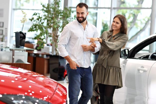 Immagine di una coppia adulta che sceglie una nuova auto nello showroom