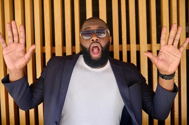 Una foto di un uomo afroamericano con gli occhiali da sole che sembra sorpreso