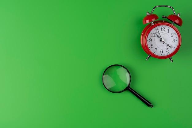 Un'immagine di sveglia e lente di ingrandimento su sfondo verde con spazio di copia, concetto di tempo di ricerca